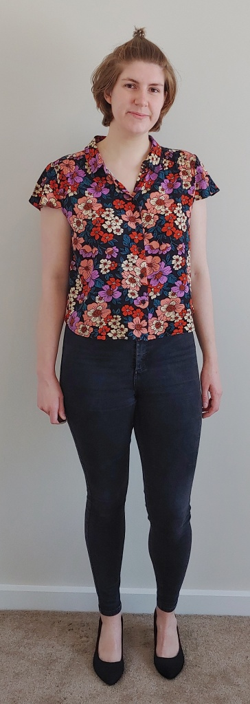 Full length photo of Helen wearing a shirt printed with anenome like flowers in pinks, purples, and oranges on a black background with green leaves, over a pair of black jeans and wearing high-heeled pointed black shoes.