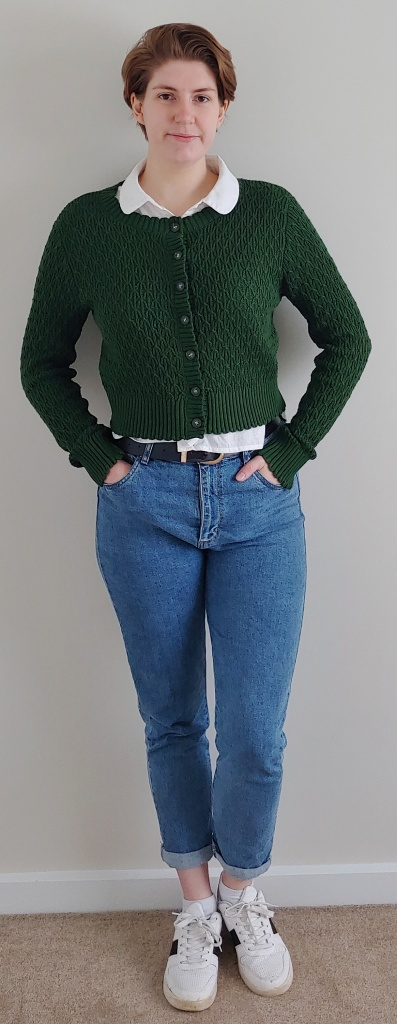 Full length photo of Helen wearing a dark green cardigan over a white shirt, with blue jeans and white sneakers.