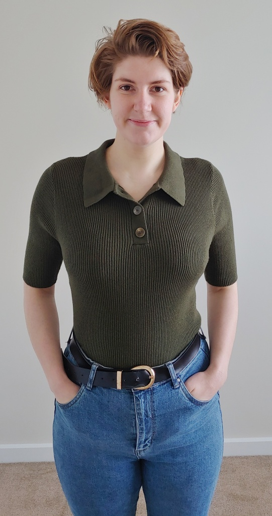 Photo of Helen wearing a dark khaki green ribbed knitted top with elbow length sleeves, a collar, and tortoiseshell buttons on the collar; the top is tucked into blue jeans.