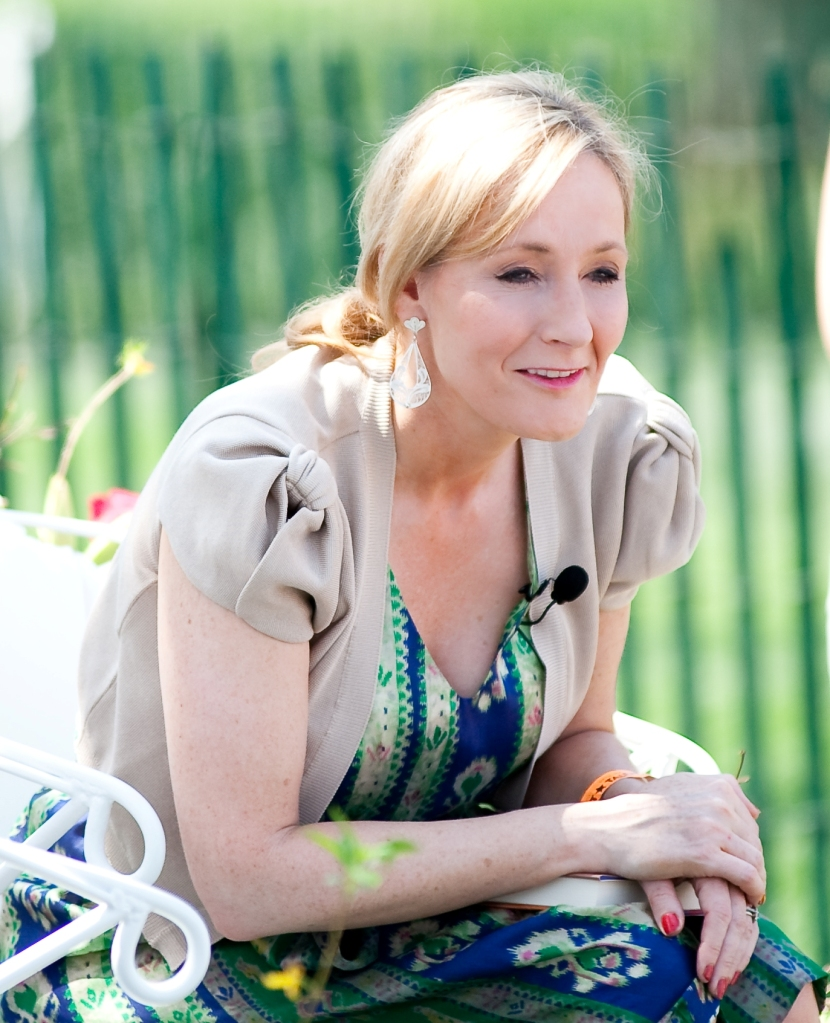 J K Rowling with blonde hair leaning forward wearing a beige jacket over a blue, green and white printed top.