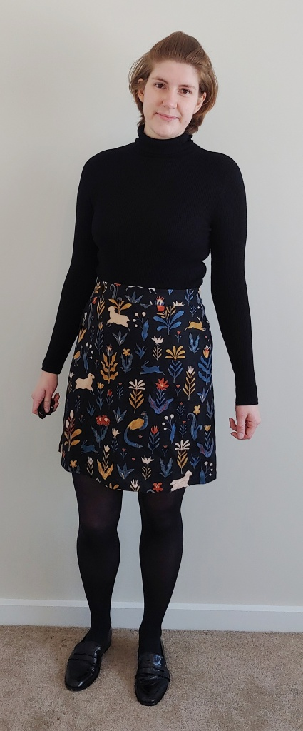 Full length photo of Helen wearing a black polo-neck top with an above the knee length black A-line skirt with flower, sheep, peacock and leaf print details.