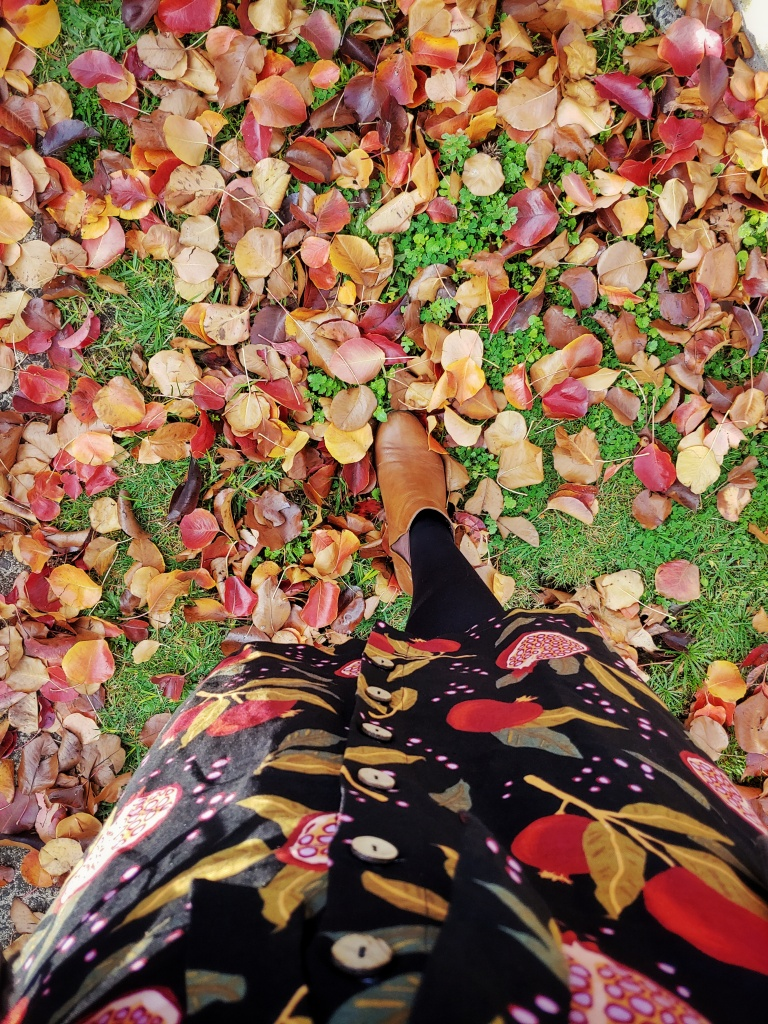 Shot by Helen looking down at the black pomegranate printed skirt and brown ankle boots, standing on grass covered in brightly coloured autumnal leaves.