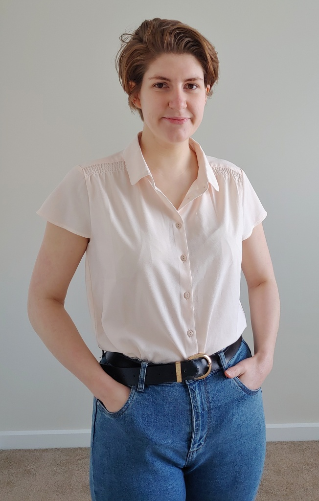 Helen wearing a peachy-cream, capped sleeved shirt with ruched details at the shoulders and a collar, with blue jeans and a black belt.