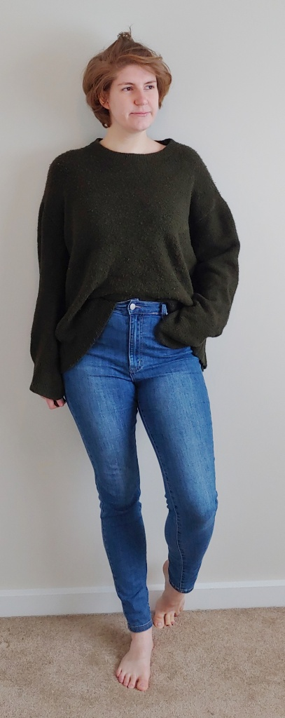 Full length photo of Helen wearing a chunky oversized khaki green jumper, with blue skinny jeans.