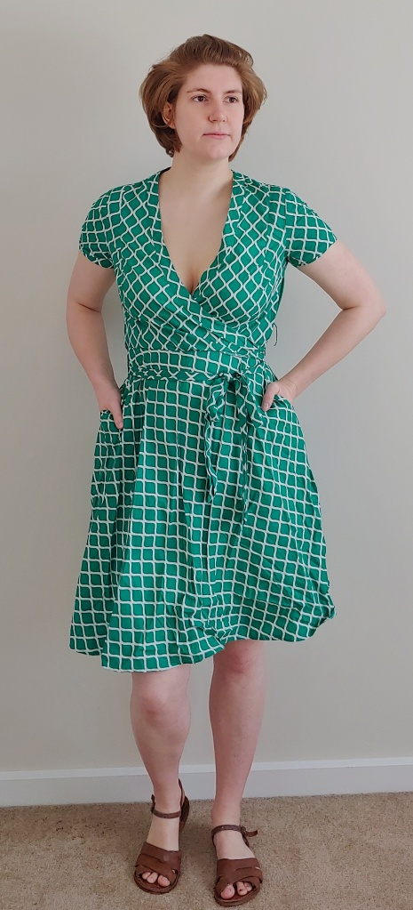 Full length photo of Helen wearing a green a-line wrap dress with a white trellis pattern.