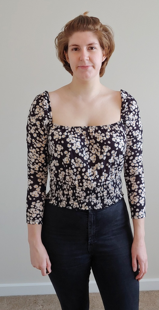 Helen wearing a long-sleeved, square neck top with ruched hemline, in a black fabric with small yellow, ditsy daisy print.
