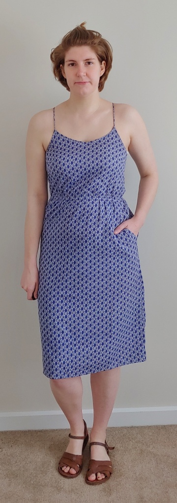 Full length photo of Helen wearing a blue dress with white netting-print, with pockets.