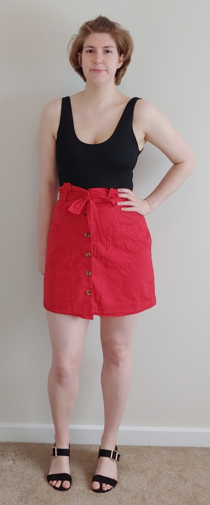 Full length photo of Helen wearing a bright red A-line skirt mini-skirt with a black vest top.