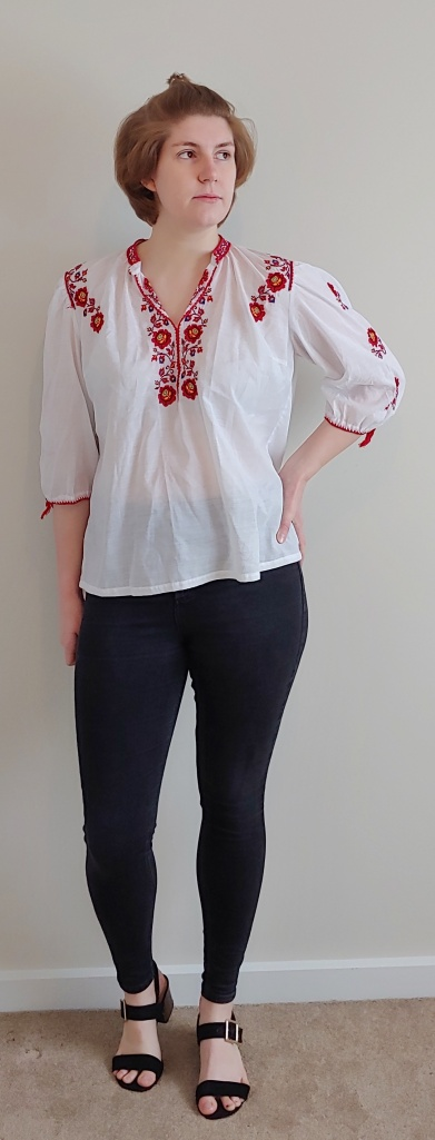 Helen wearing a baggy white tip with half-length sleeves and red and yellow floral embroidery around the collar and on the sleeves.