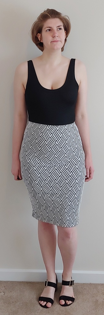 Full length photo of Helen wearing a zig-zag print pencil skirt, with a black vest top and black sandals.