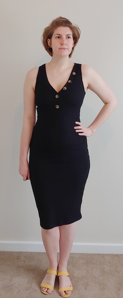 Full length photo of Helen wearing a black, ribbed sleeveless dress, with large buttons down a v-neckline, with yellow sandals.