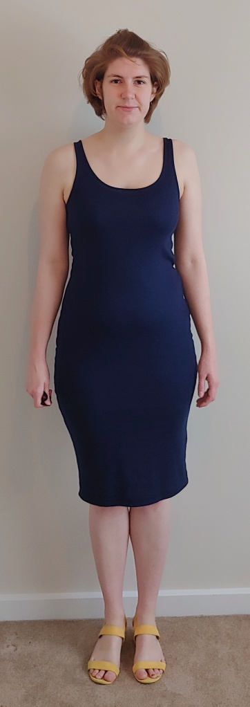 Helen wearing a long navy dress top, with yellow strappy sandals.