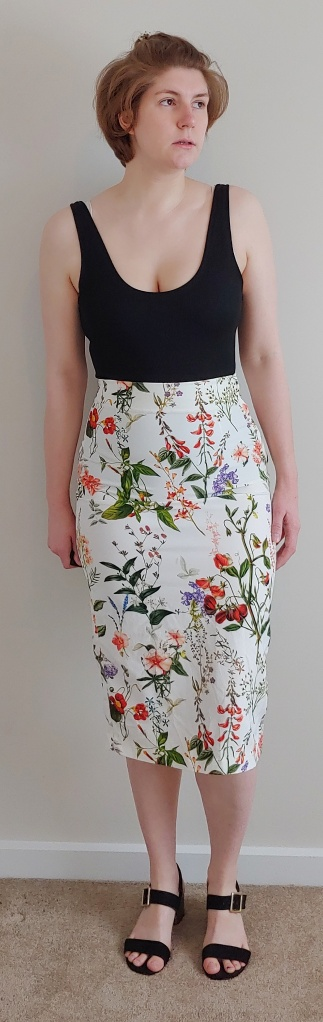 Full length photo of Helen wearing a high waisted botanical print skirt with a black vest top.
