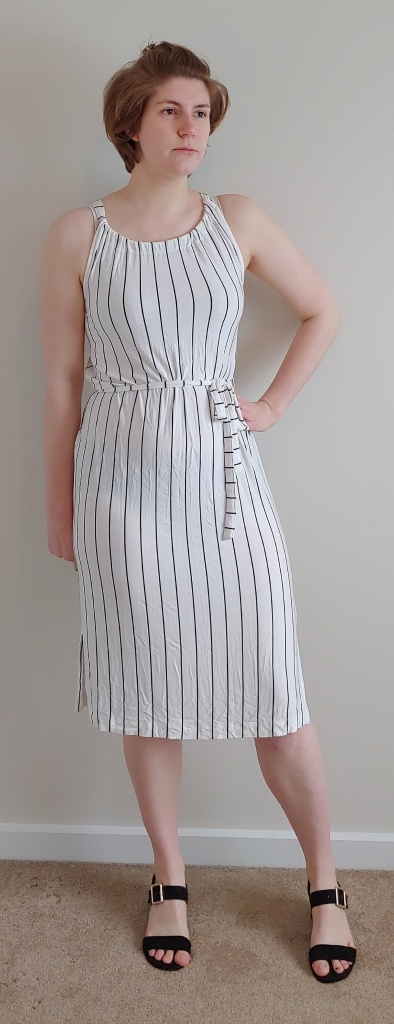 Full length photo of Helen wearing a white with thin black stripes knee-length dress with a belt in the same fabric around the waist, and black sandals.
