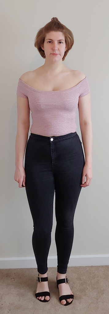 Full length image of Helen wearing a cream and red thin-striped crop top over black skinny jeans.