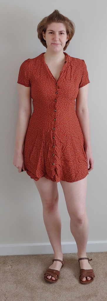 Full length photo of Helen wearing a rust-coloured short tea-dress with white polka dots.