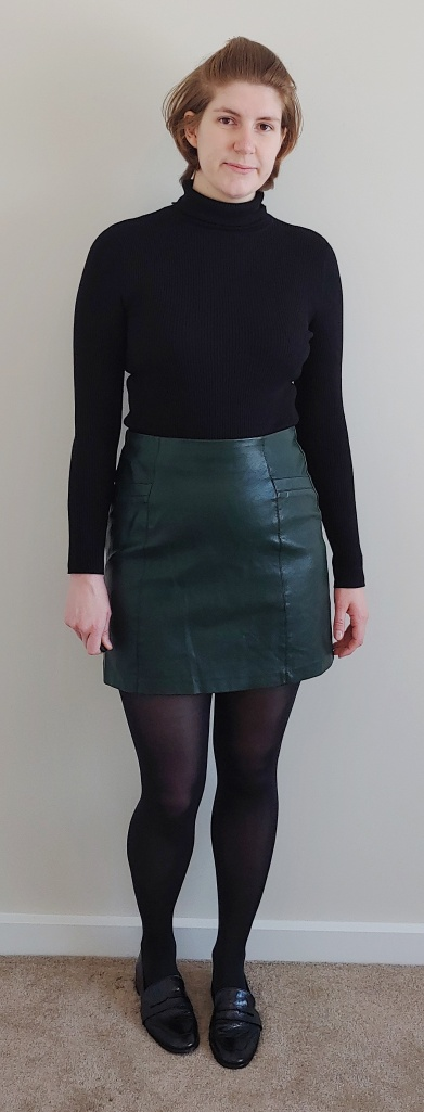 Full length photo of Helen wearing an above-the-knee A-line dark green faux leather skirt with a black ribbed turtle neck top and black flat pumps.