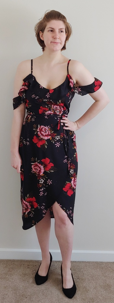 Full length photo of Helen wearing a knee-length wrap-style dress in black with red and pink floral print.
