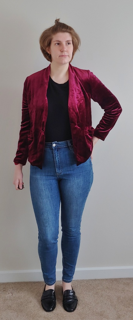 Full length photo of Helen wearing a rich, berry-pink velvet jacket, over a black top and blue jeans.