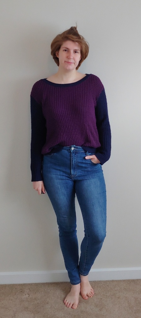 Full length photo of Helen wearing a chunky knit jumper over blue jeans.  The jumper has navy sleeves and a navy strip around the boat neckline, the rest being a plummy purple colour.