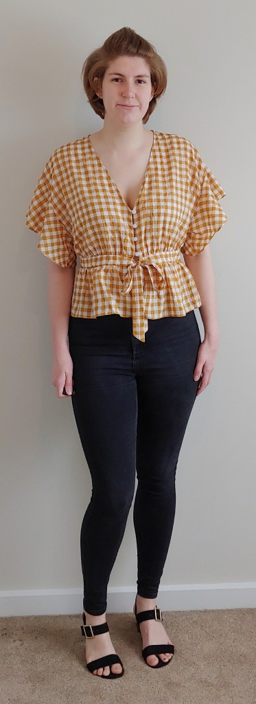 Full length photo of Helen wearing a yellow and white gingham top with floaty short sleeves and a peplum waist with tie, and black jeans.