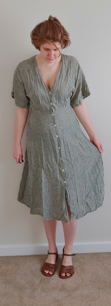 Full length photo of Helen wearing a light mossy-green dress with thin vertical white stripes, wide elbow-length sleeves, and an A-line, over the knee skirt part.