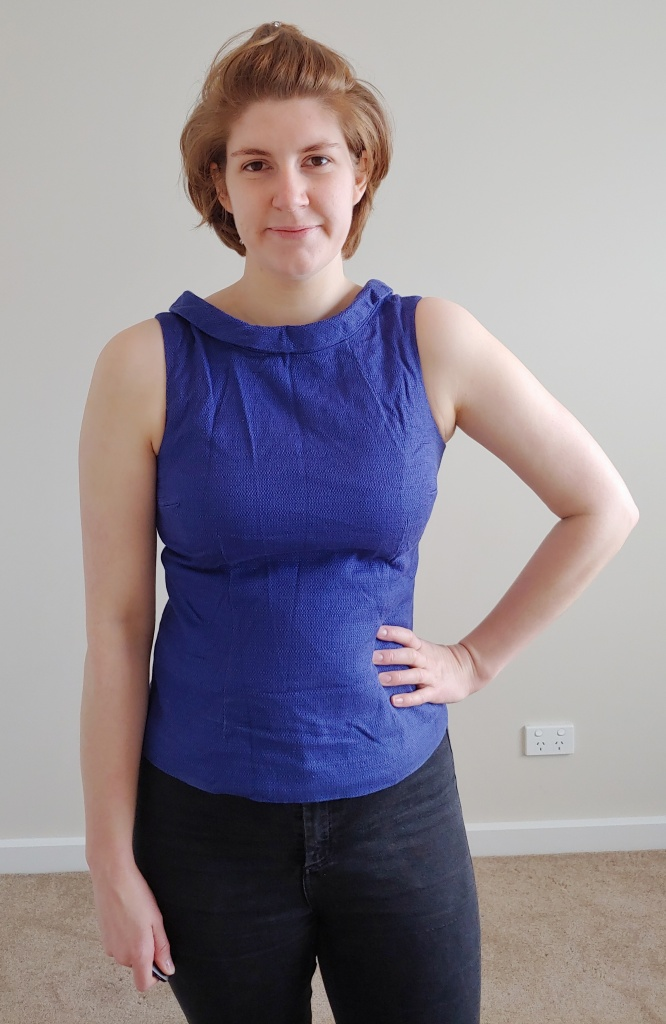 Helen wearing a rich blue sleeveless shell top with a folded wide collar.