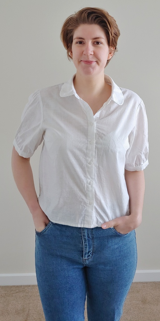 Helen wearing a white shirt with short sleeves and a Peter Pan collar, with blue jeans.
