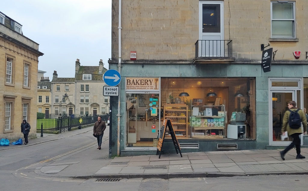 The front of Thoughtful Bakery, Bath, with shelves of food visible inside, and a Georgian Street down the side