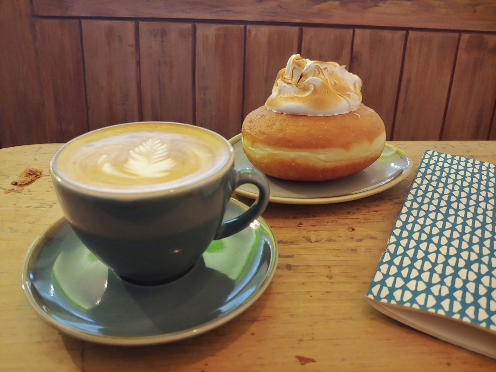 Blue coffee cup with froth, and a doughnut with a large meringue topping, on a wooden table next to a blue and white printed notebook.