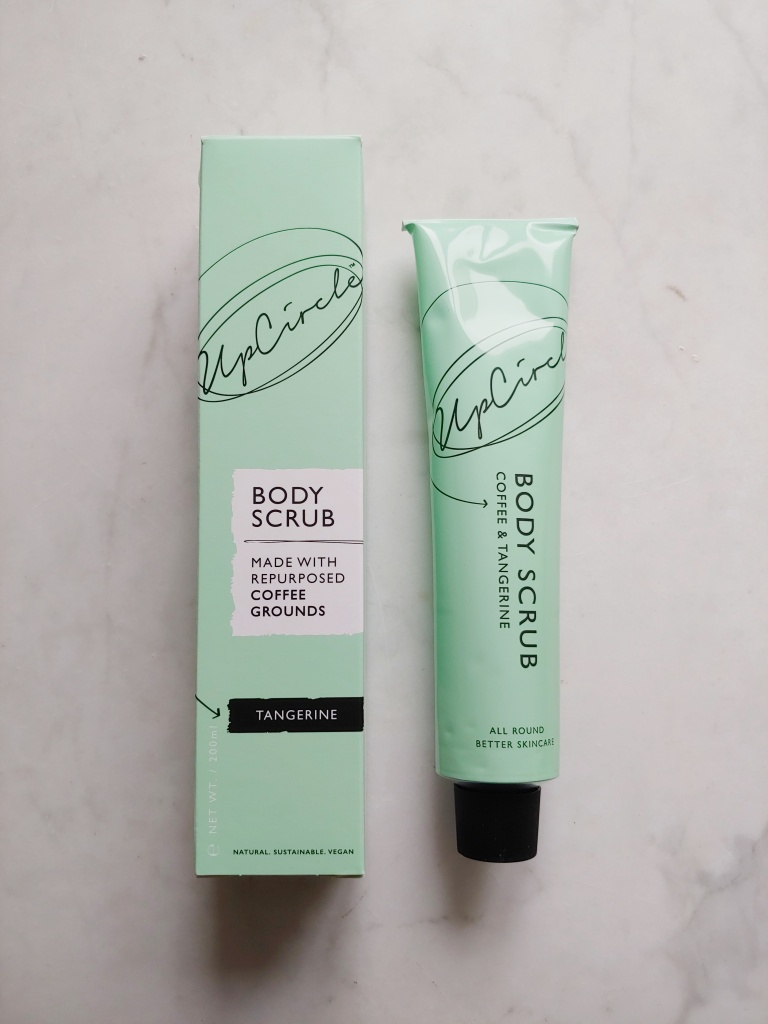 Photo of coffee scrub in a mint-green tube against a marble background.