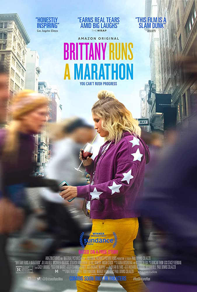 Movie poster for Britanny Runs a Marathon, with Brittany holding her phone and drinking from a wine glass through a straw walking to the left, and blurred people running either side of her to the right of frame.
