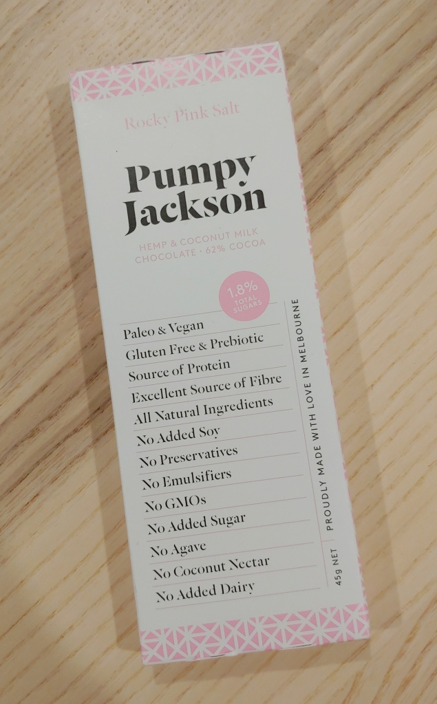 Photo of a long, narrow cardboard box of chocolate, with 'Pumpy Jackson' in a large, bold font, with text down the front, and a pink geometric print around the edges.