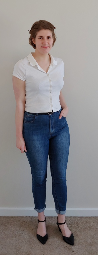 Full length photo of Helen wearing rolled up blue jeans with a white button-up polo shirt, a black belt, and black pointed open shoes.