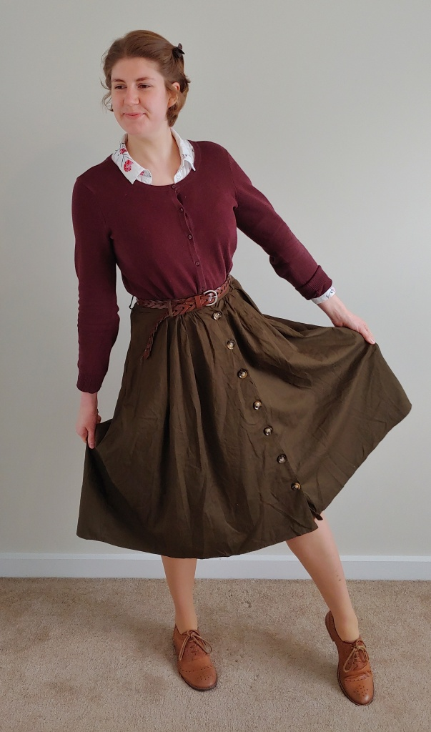 Full length photo of Helen in a khaki mid-length skirt with buttons down the front, and a burgundy cardigan over a white and floral print shirt, with brown brogues.