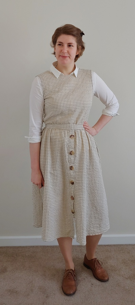 Full length photo of Helen wearing a light yellow/green and cream gingham dress over a white shirt with the sleeves rolled up, with brown brogues.