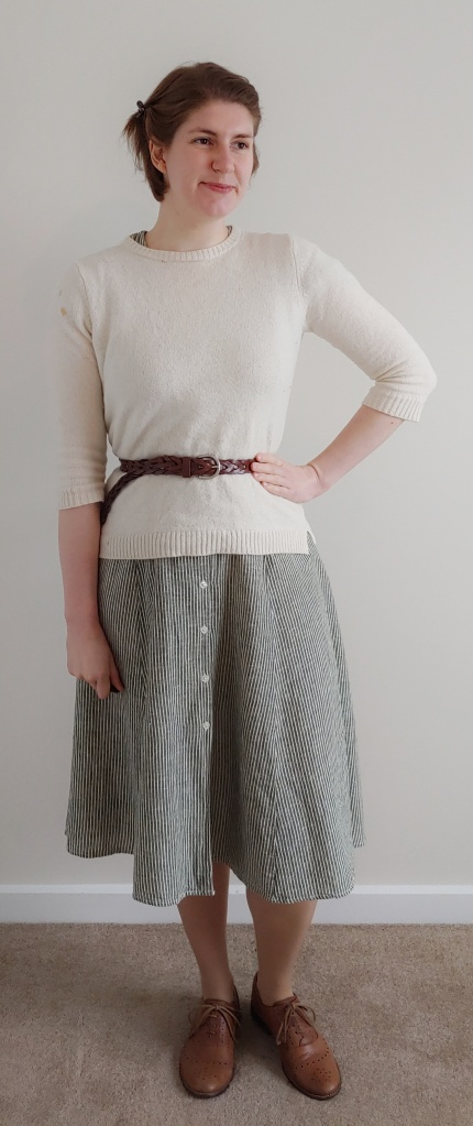 Full length photo of Helen wearing a green and thin white striped dress with a cream jumper over the top, with a brown belt at the waist and brown brogues.