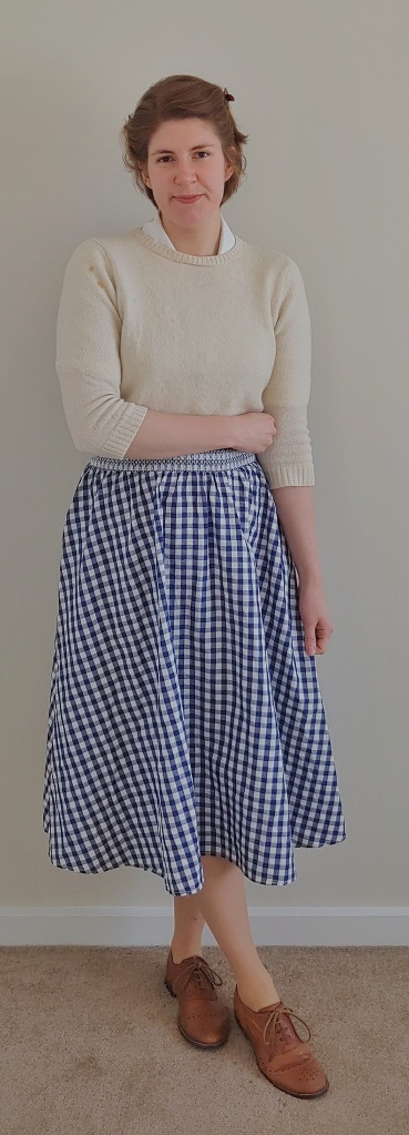 Full length photo of Helen wearing a cream half-length sleeved jumper over a cream shirt, with a blue and white gingham midi length circle skirt