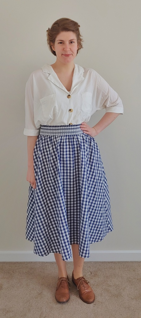 Full length photo of Helen wearing a cream half-sleeved shirt with a blue and white gingham knee length circle skirt.