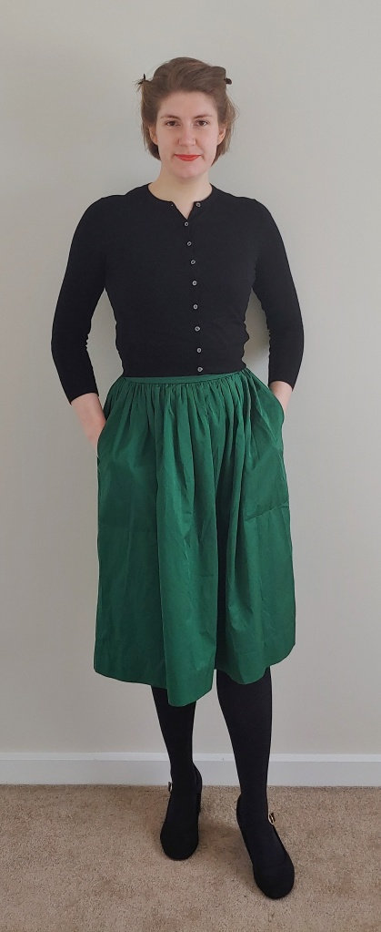 Full length photo of Helen wearing a dark green silky skirt with a cropped black cardigan, black tights and black Mary-Jane heels.