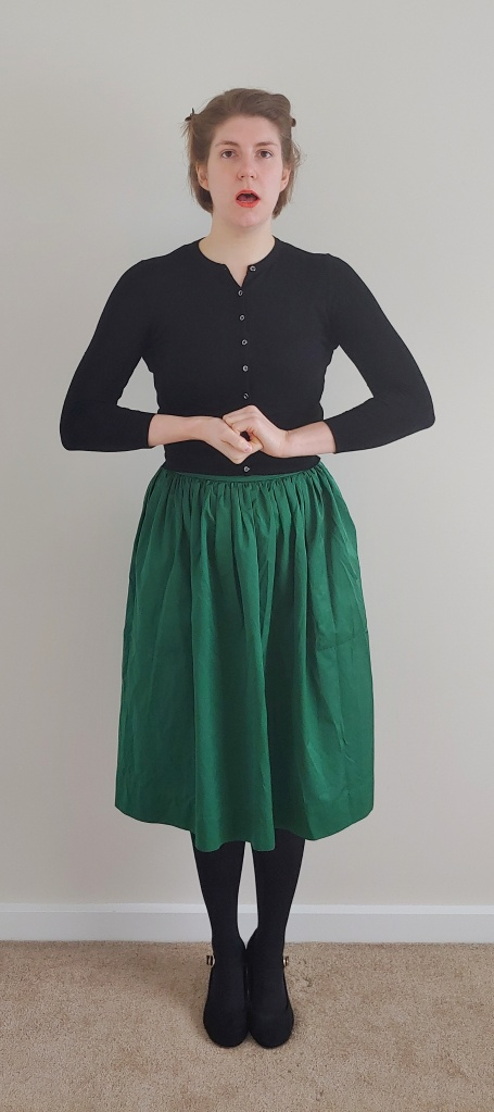 Full length photo of Helen wearing a dark green silky skirt with a cropped black cardigan, black tights and black Mary-Jane heels, stood with hands clasped in front of her and mouth open as if singing.