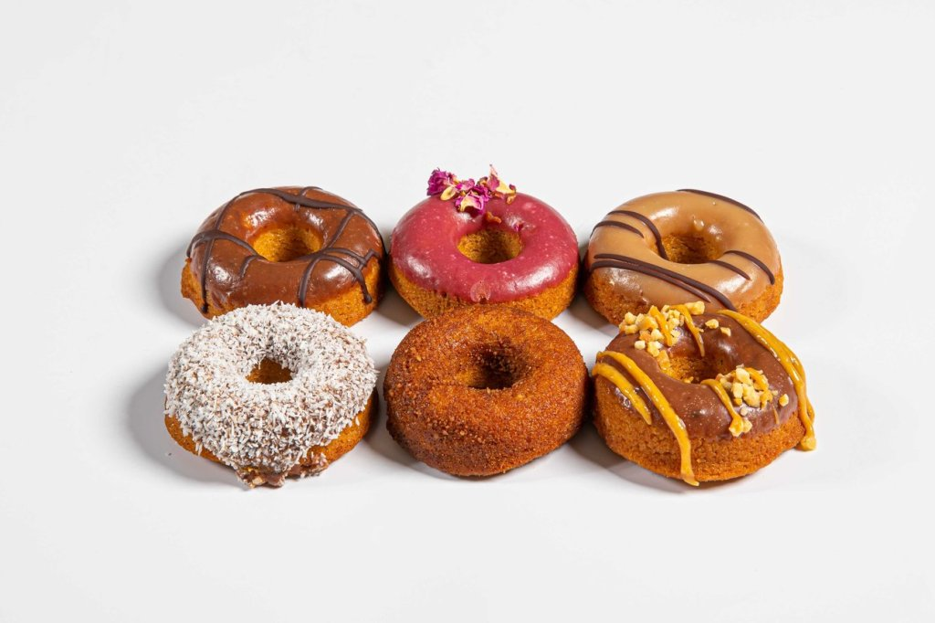 Six small doughnuts with different toppings, including a pink one, a Lamington one, and salted caramel.