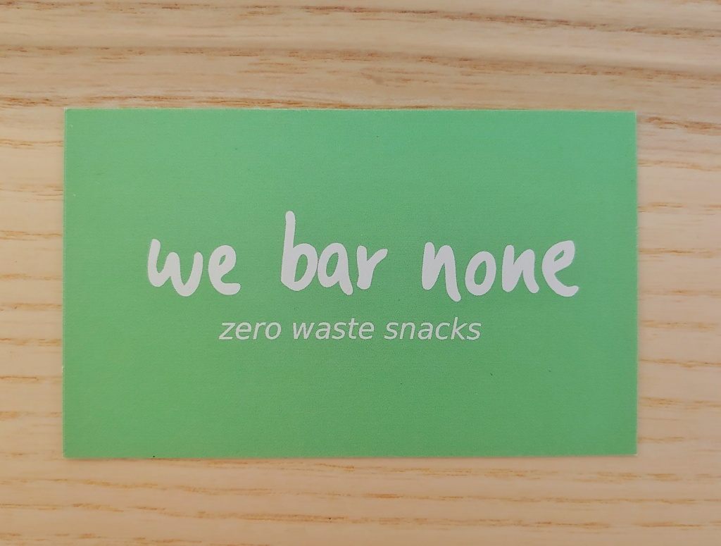 Business card with 'we bar none' in a hand written style font, with 'zero waste snacks' underneath in a arial type font, both in white on a minty green background.