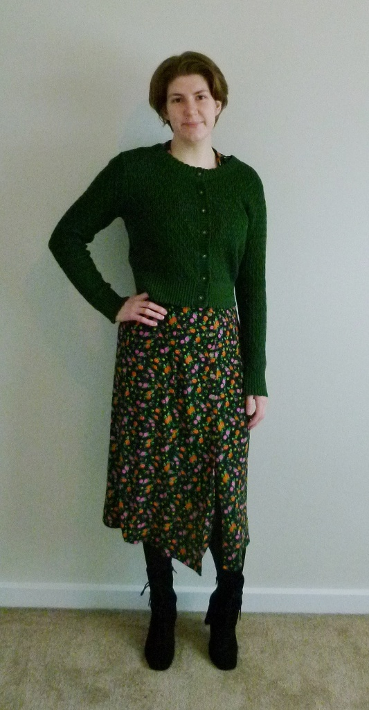 Full length photo of Helen wearing a long black with green, orange and pink ditsy print dress, with a slightly cropped green cardigan over the top, and lace-up suede boots.