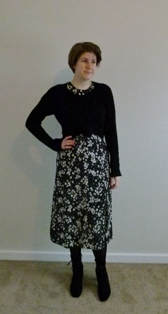 Full length photo of Helen in the same dress with a long-sleeved black jumper knotted at the waist over the top.