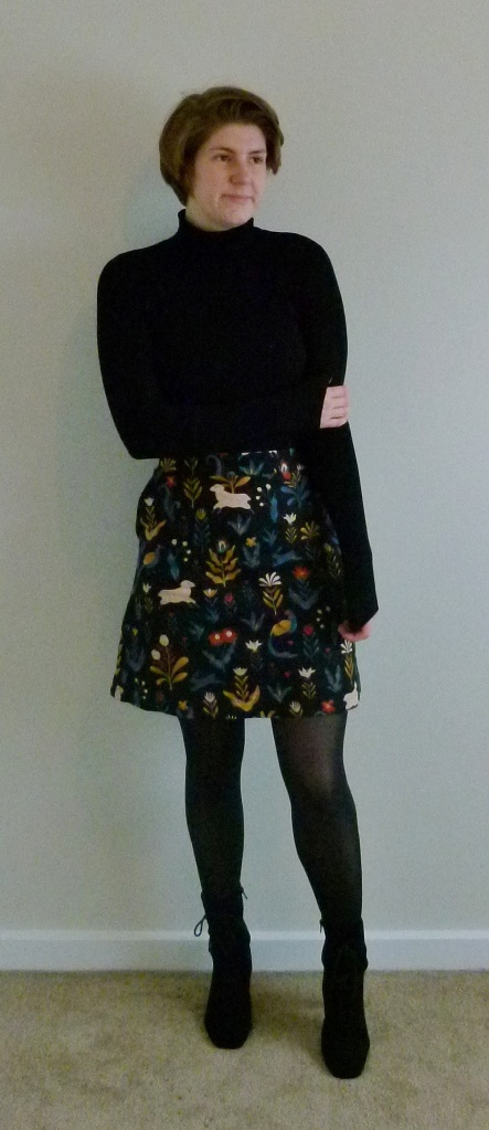 Full length photo of Helen wearing a black turtle neck top with an A-line short skirt in a flower and animal print, with black tights and black lace-up suede boots.