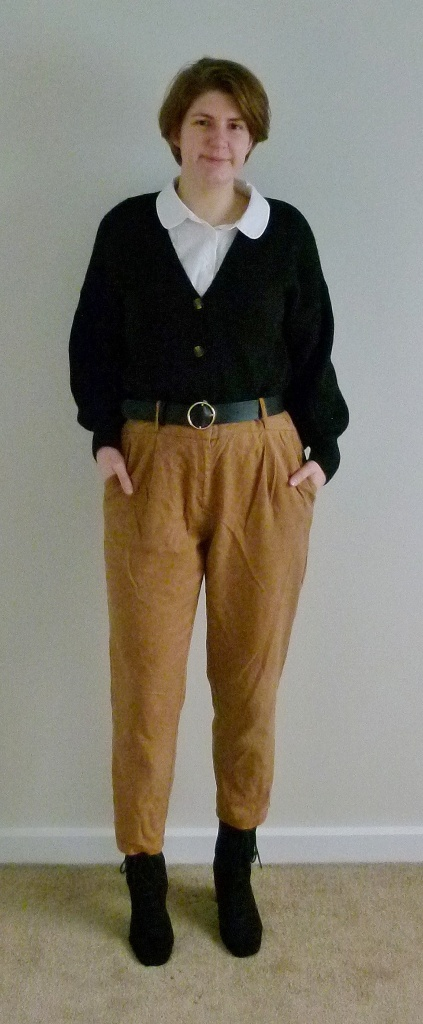 Full length photo of Helen wearing a Peter Pan collared white shirt with a black, wide-sleeved cardigan, tan high-waisted loose fitting trousers, and the same suede lace-up boots.