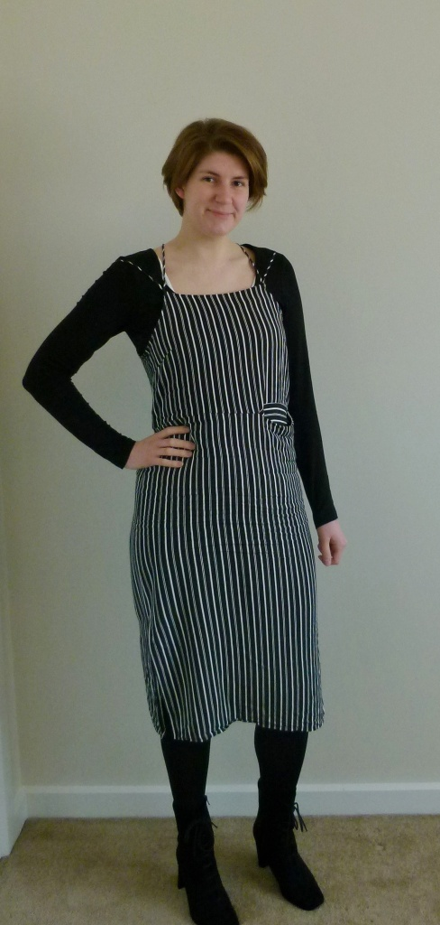 Full length photo of Helen wearing a black and white vertical striped slip-dress over a long-sleeved black t-shirt, with black tights and black suede lace-up boots.