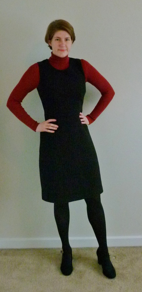 Full length photograph of Helen wearing a dark orange turtle-neck top with a black, knee-length pinafore dress, black tights, and black Mary Jane court shoes with a gold buckle.