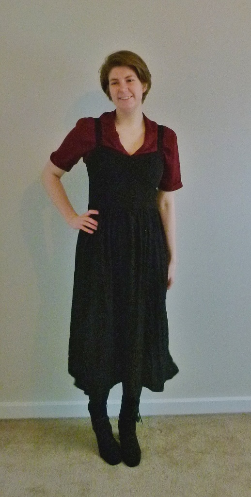 Full length photo of Helen wearing an ox-lood short sleeved shirt, with a black apron-style dress with a wide skirt over the top, black tights, and suede lace-up high-heeled boots.
